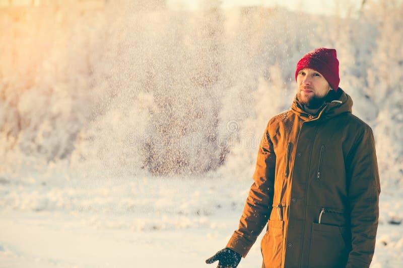 Jeune homme appréciant la marche de temps de neige extérieure image stock