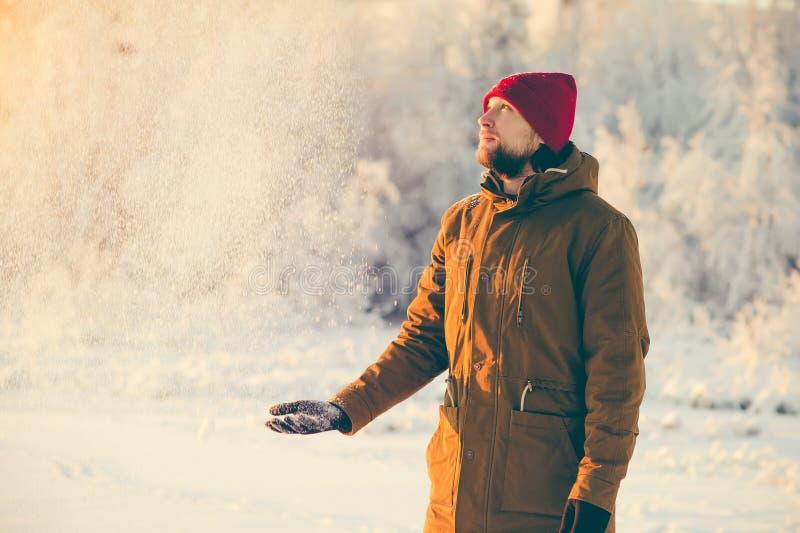 Jeune homme appréciant la marche de temps de neige extérieure images stock