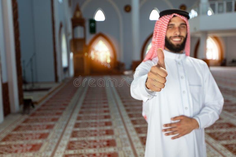 Jeune homme Arabe de sourire posant à l'intérieur de la mosquée photographie stock