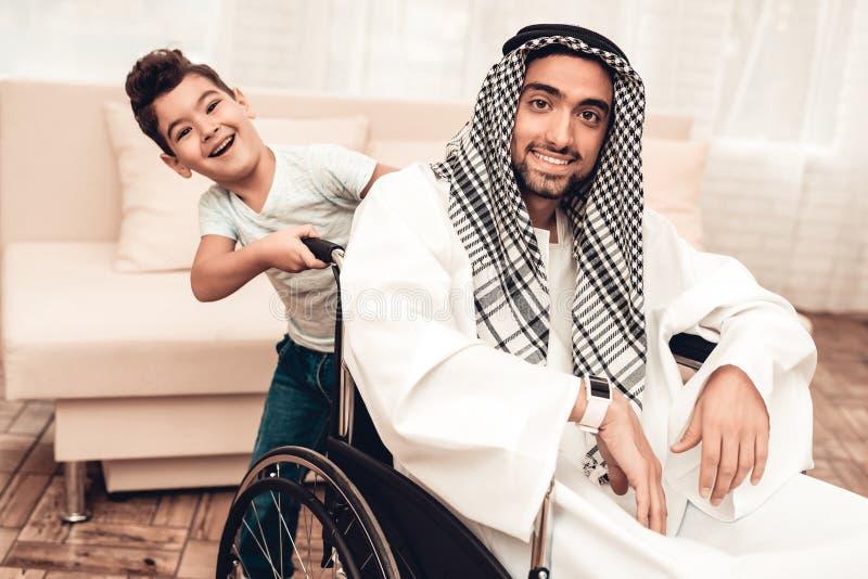 Jeune homme Arabe sur le fauteuil roulant avec le fils de sourire photo stock