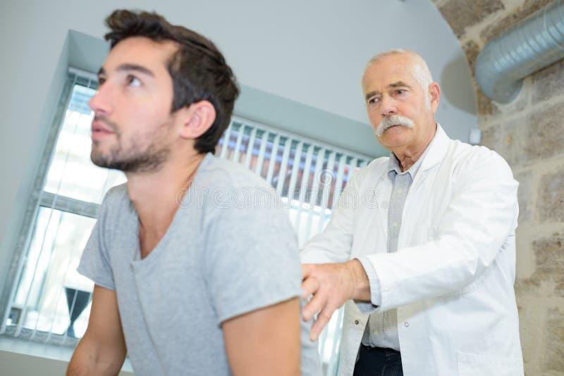 Jeune homme arrière de examen de stimulant de docteur mûr photo libre de droits