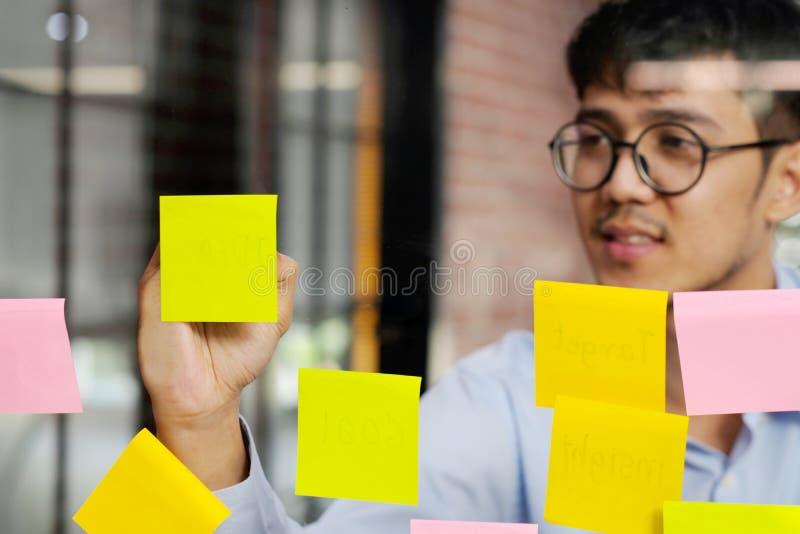 Jeune homme asiatique écrivant sur la note collante au bureau, affaires faisant un brainstorm des idées créatives, mode de vie de photographie stock libre de droits
