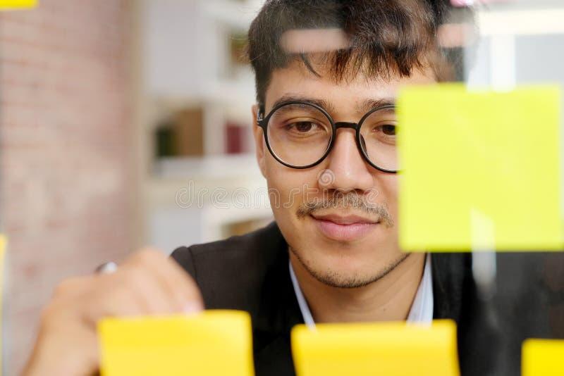 Jeune homme asiatique écrivant sur la note collante au bureau, affaires faisant un brainstorm des idées créatives, mode de vie de photos stock