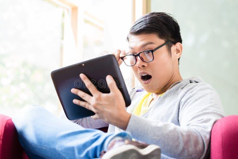 Jeune homme asiatique étonné par la documentation en ligne montrée sur une tablette photos stock