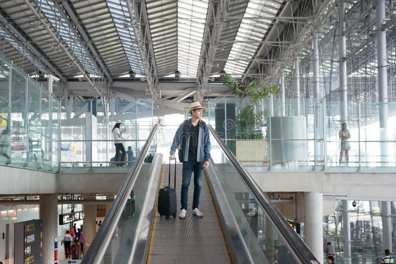 Jeune homme asiatique avec le bagage en bas de l'escalator dans l'aéroport photos stock