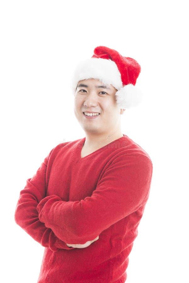 Jeune homme asiatique avec le chapeau de Noël d'isolement sur le blanc photo stock