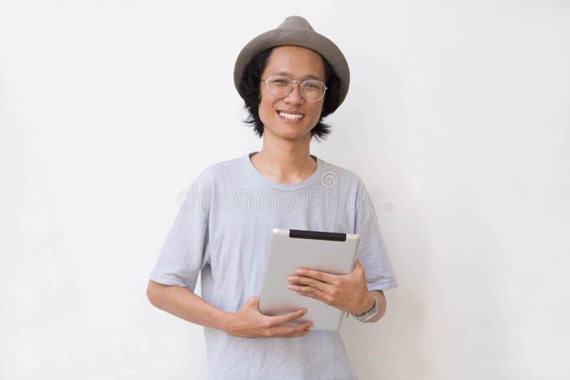 Jeune homme asiatique avec le chapeau et les verres de chapeau feutré utilisant le comprimé et sourire à la caméra tenant un PC d photographie stock libre de droits