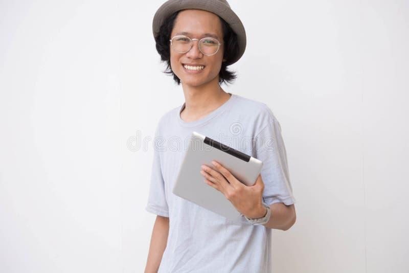 Jeune homme asiatique avec le chapeau et les verres de chapeau feutré utilisant le comprimé et sourire à la caméra tout en tenant image libre de droits