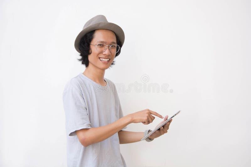 Jeune homme asiatique avec le chapeau et les verres de chapeau feutré utilisant le comprimé et le sourire images libres de droits