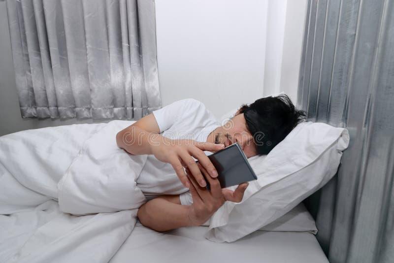 Jeune homme asiatique avec le smartphone se couchant sur le lit dans la chambre à coucher Symptômes de Nomophobia ou aucun concep image stock
