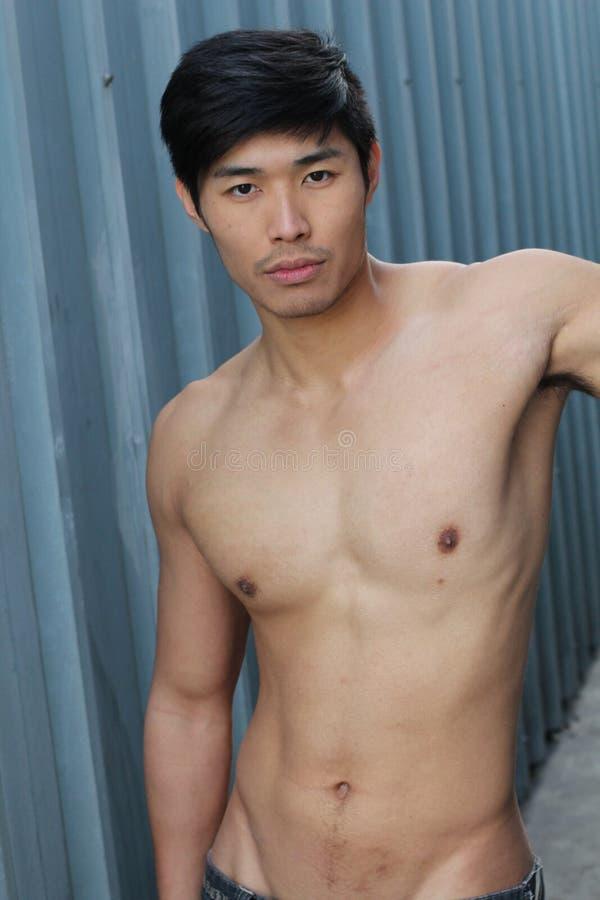 Jeune homme asiatique avec le torse musculaire image stock
