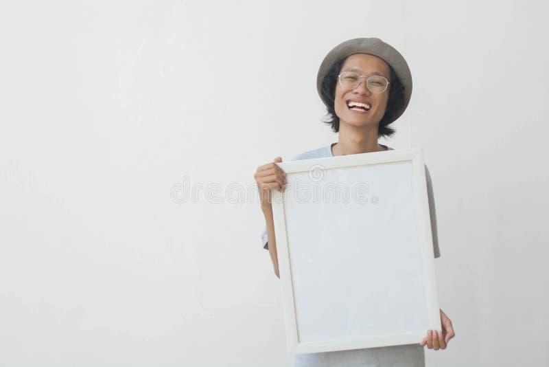 Jeune homme asiatique avec les verres et le chapeau tenant le conseil blanc et souriant à la caméra images stock