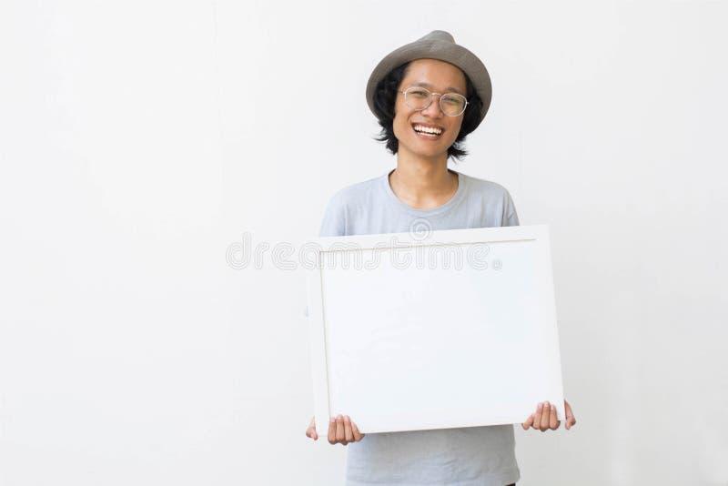 Jeune homme asiatique avec les verres et le chapeau tenant le conseil blanc et souriant à la caméra photo stock