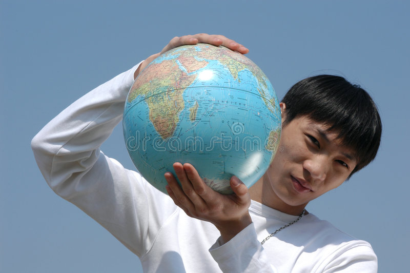 Jeune homme asiatique avec un globe image stock