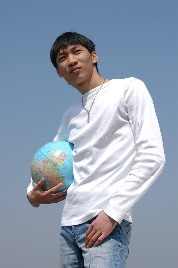 Jeune homme asiatique avec un globe photos stock