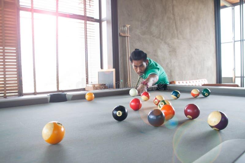 Jeune homme asiatique beau jouant la piscine à la maison, foyer sélectif images stock