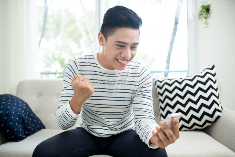 Jeune homme asiatique bel employant la séance futée mobile moderne de téléphone photo stock