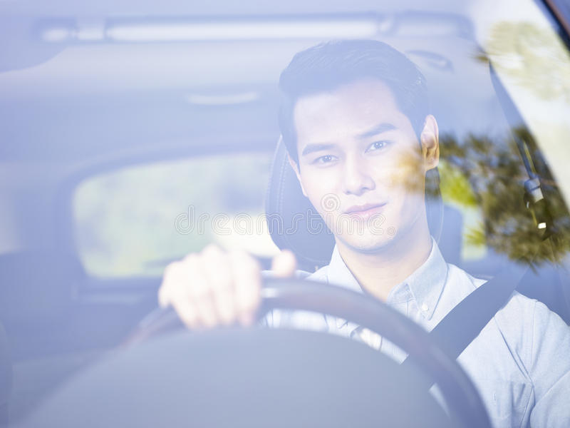Jeune homme asiatique conduisant une voiture images stock