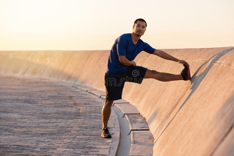 Jeune homme asiatique convenable étirant ses jambes avant une course photographie stock libre de droits
