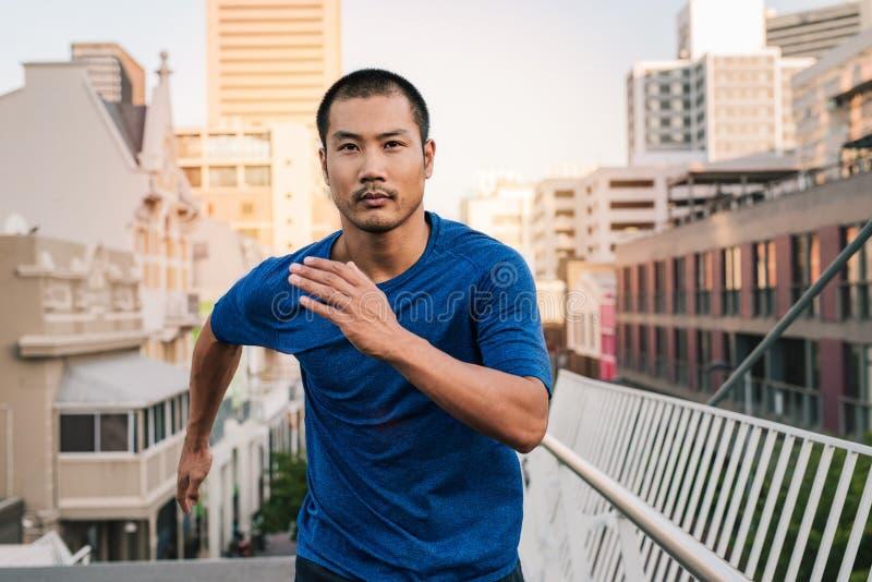 Jeune homme asiatique convenable courant par la ville photographie stock
