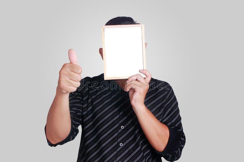 Jeune homme asiatique couvrant son visage de petit tableau blanc image libre de droits