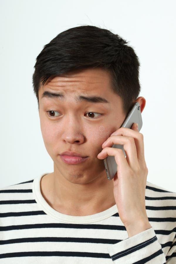 Jeune homme asiatique déçu à l'aide d'un smartphone images libres de droits
