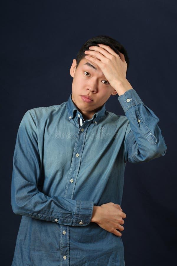Jeune homme asiatique déçu couvrant son front par la paume images stock