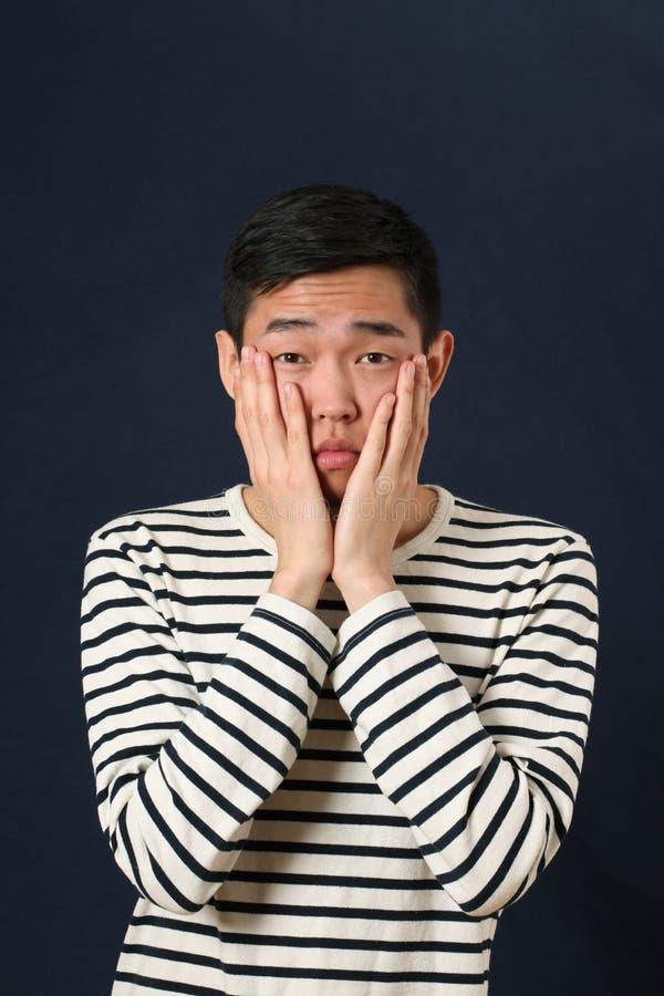 Jeune homme asiatique déçu couvrant son visage par des paumes photos libres de droits