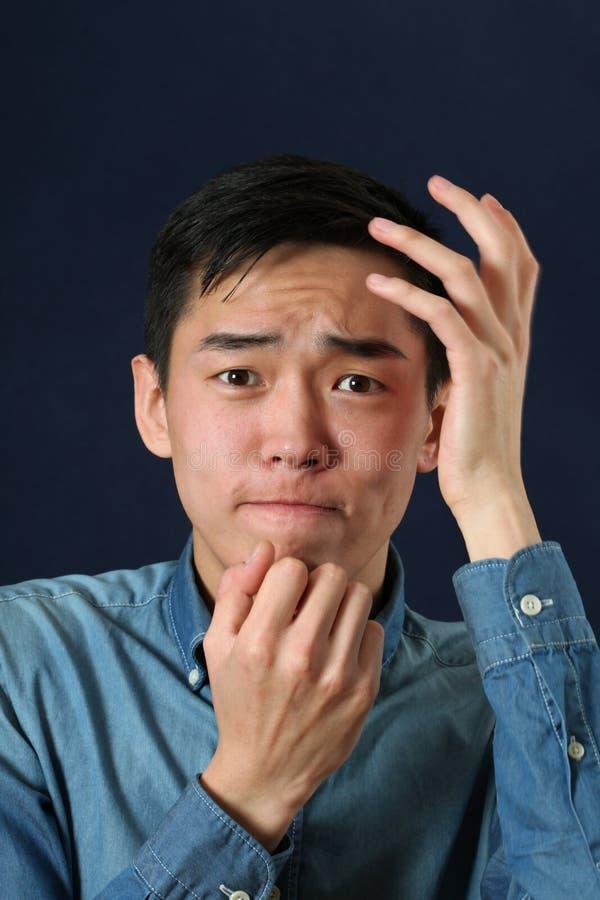 Jeune homme asiatique déçu regardant l'appareil-photo images libres de droits