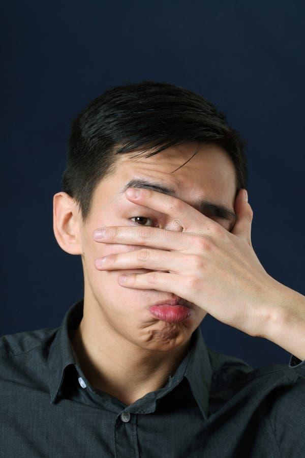 Jeune homme asiatique déçu regardant l'appareil-photo par son finge photos stock