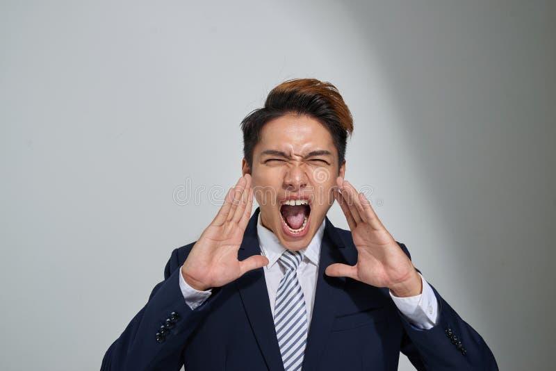 Jeune homme asiatique d'affaires criant avec des mains évasées à sa bouche, d'isolement sur le fond gris photographie stock libre de droits
