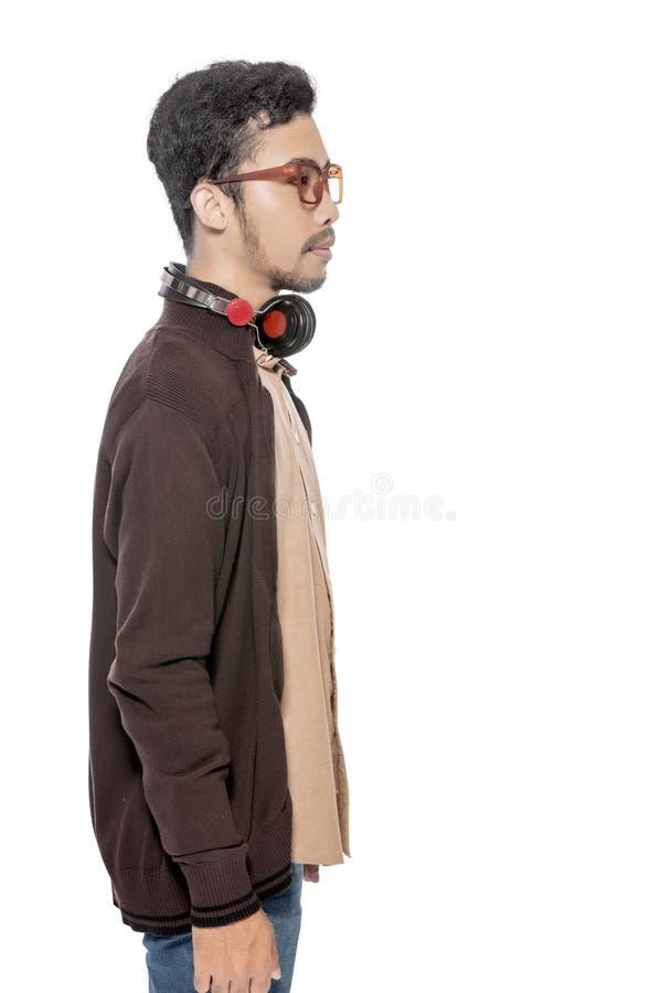 Jeune homme asiatique dans la position brune de veste avec des écouteurs sur son cou photo libre de droits