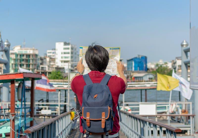Jeune homme asiatique de sac à dos en tant que touriste regardant le travell de carte image stock