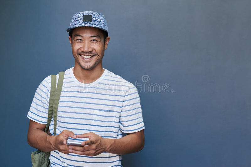 Jeune homme asiatique de sourire à l'aide d'un téléphone portable dehors photos stock
