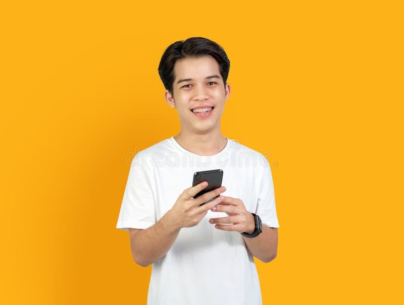Jeune homme asiatique de sourire avec le téléphone intelligent de participation sur le fond orange l'espace de copie pour la publ photographie stock