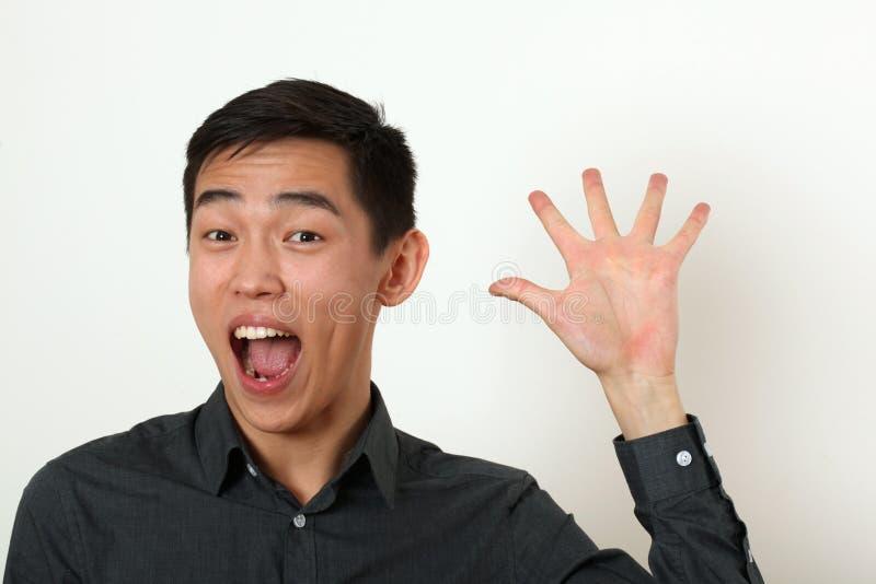 Jeune homme asiatique de sourire ondulant sa paume et regarder l'appareil-photo image libre de droits