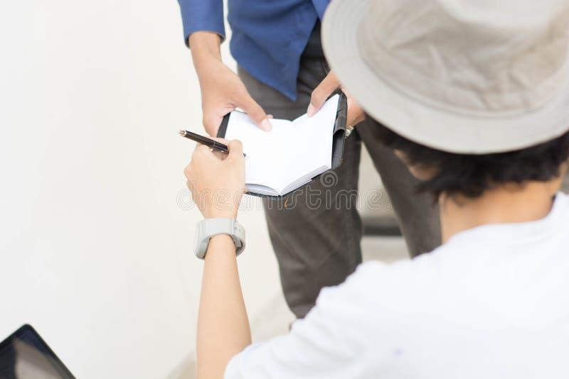 Jeune homme asiatique de vue arrière avec le chapeau et les verres de chapeau feutré écrivant sur la note pour signer une certain photos libres de droits