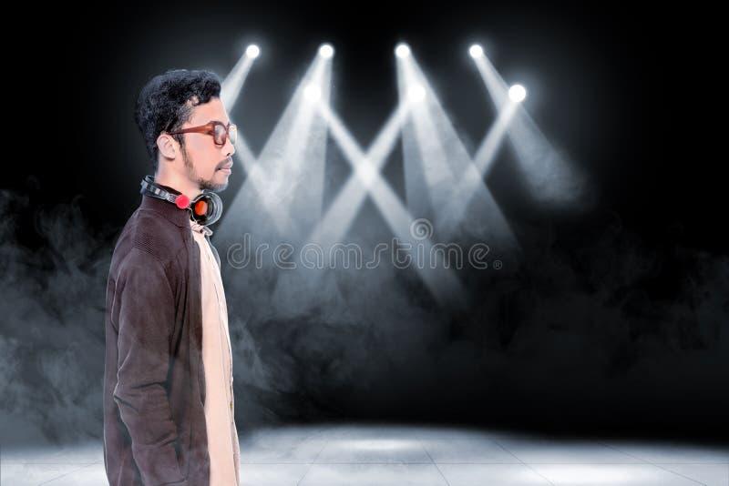 Jeune homme asiatique en verres utilisant la veste brune avec des écouteurs sur sa position de cou images stock