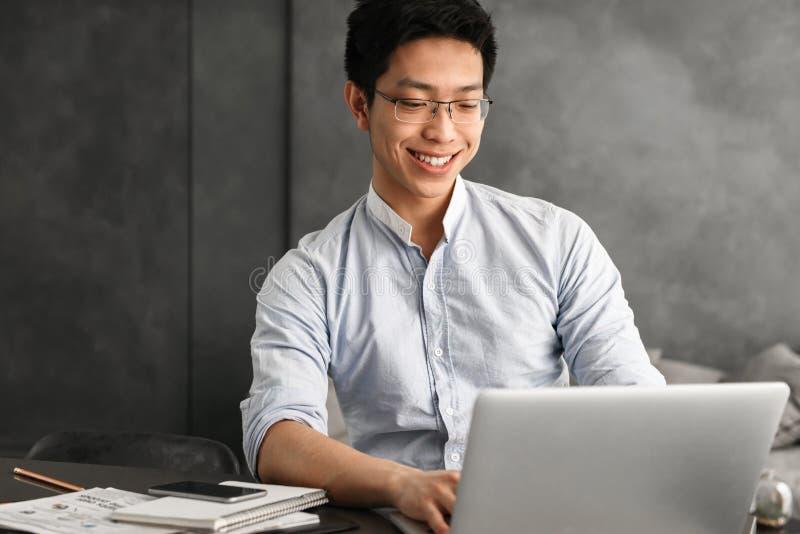 Jeune homme asiatique heureux à l'aide de l'ordinateur portable photo libre de droits