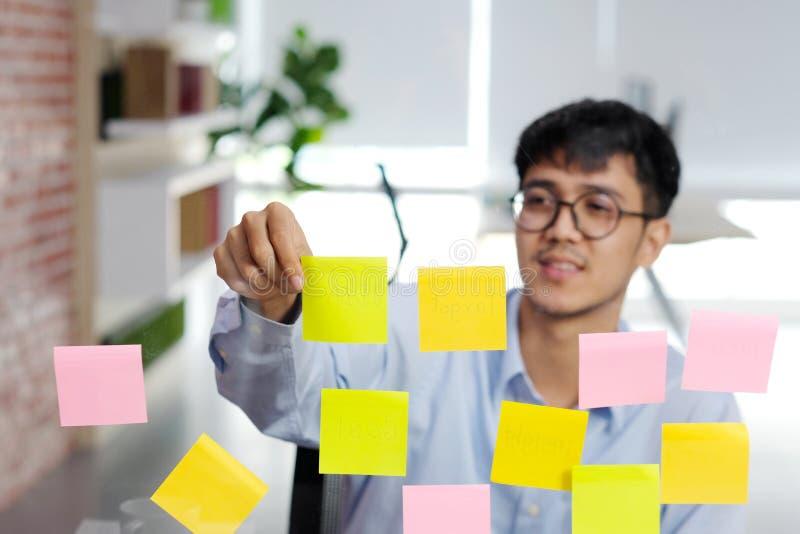 Jeune homme asiatique lisant la note collante sur le mur de verre au bureau, affaires faisant un brainstorm des idées créatives,  image libre de droits