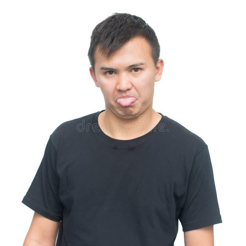 Jeune homme asiatique montrant la langue photos stock