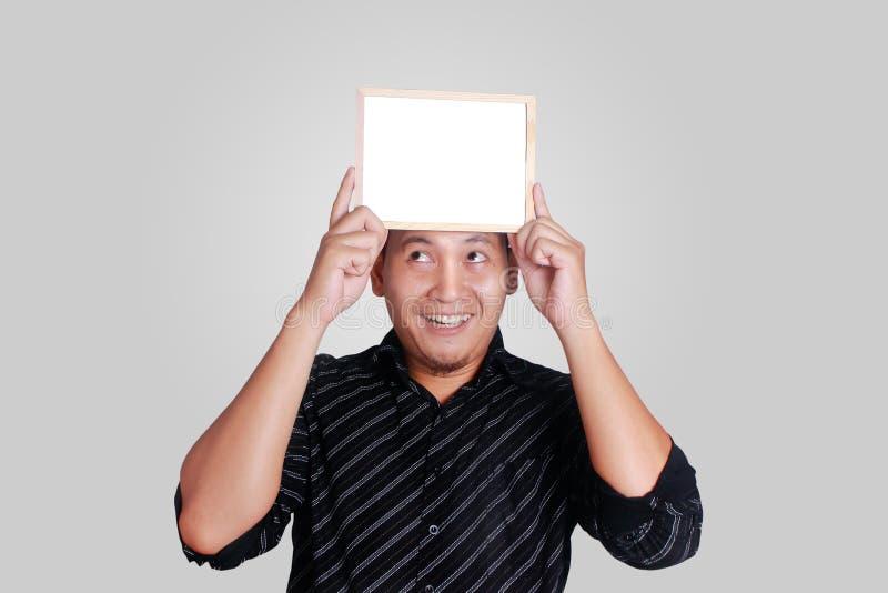 Jeune homme asiatique montrant le petit tableau blanc couvrant sa tête photos stock