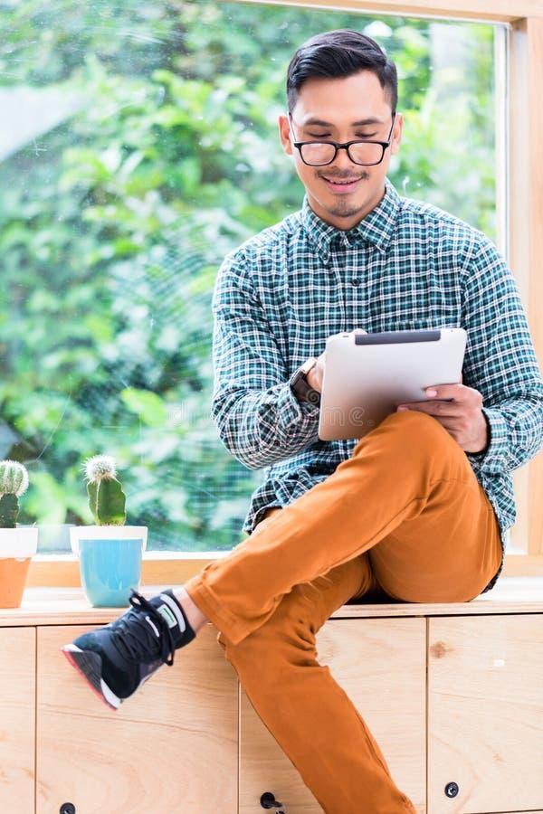 Jeune homme asiatique passant en revue l'Internet sur une tablette dans le bureau photo stock