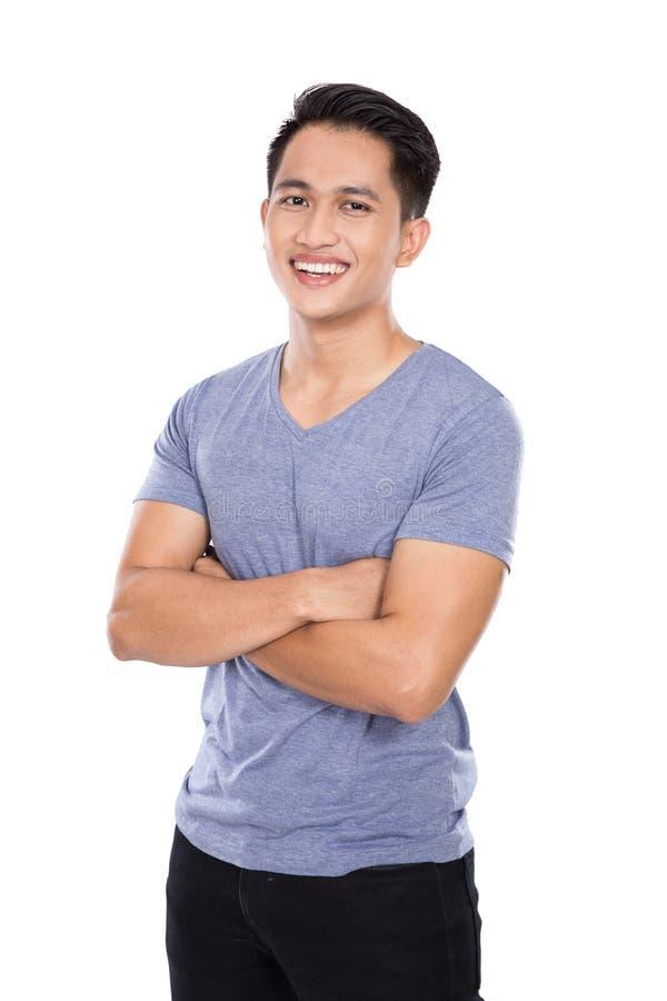 Jeune homme asiatique posant sur le fond blanc, bras croisés photographie stock libre de droits