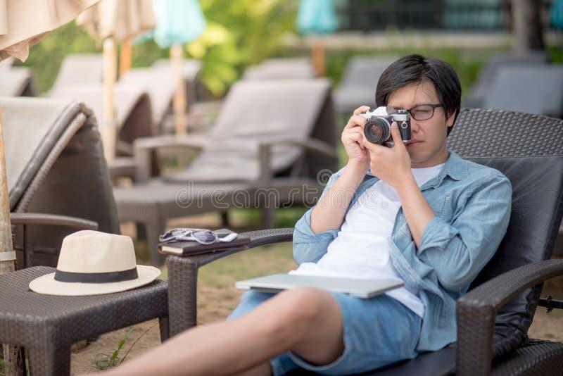 Jeune homme asiatique prenant des photos sur le banc près de la plage photos stock