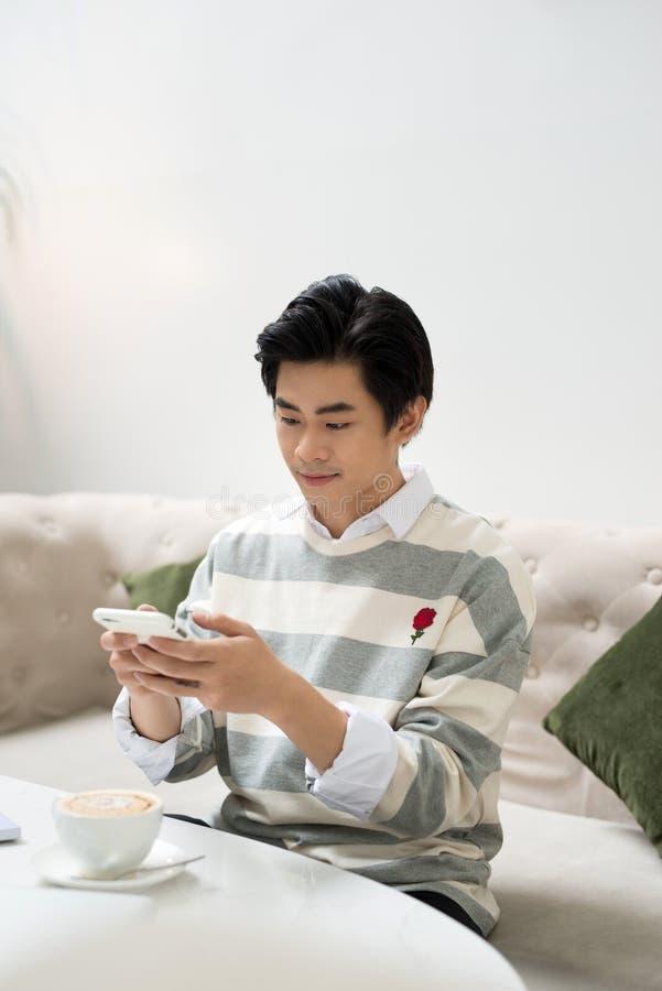 Jeune homme asiatique prenant la photo de la tasse de café pendant la pause-café photo libre de droits