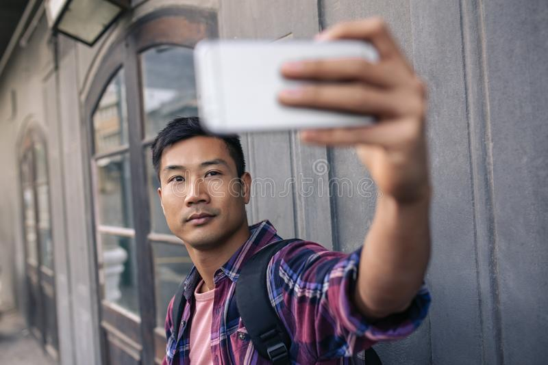 Jeune homme asiatique sûr prenant des selfies sur une rue de ville images libres de droits