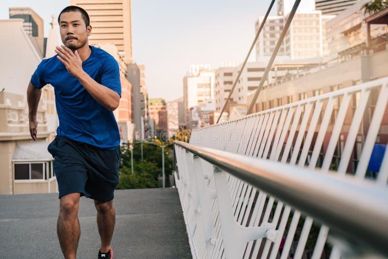 Jeune homme asiatique sportif courant par la ville photo stock