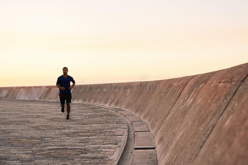 Jeune homme asiatique sportif courant sur une course de matin photo stock