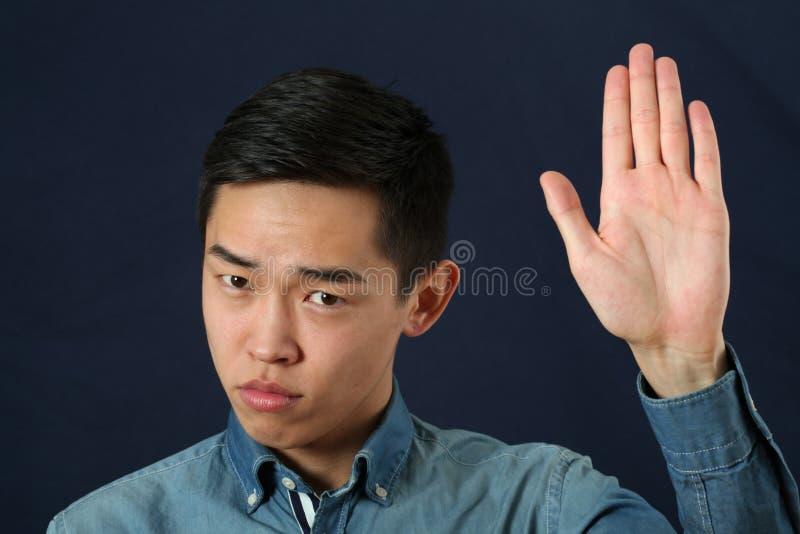Jeune homme asiatique strict donnant le signe d'arrêt photos libres de droits
